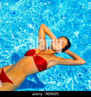 Young woman with red bikini floating on water in swimming pool, Guadeloupe, French West Indies, - Stock Photo