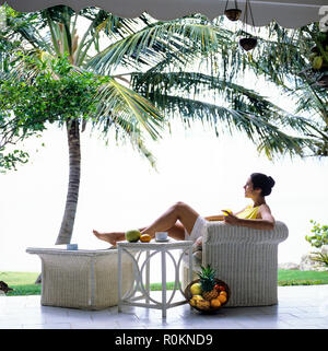Young woman relaxing in white wicker armchair, terrace, tropical garden, palm tree, Guadeloupe, French West Indies, - Stock Photo