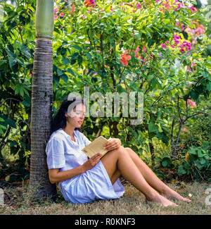 Young woman sitting in tropical garden and reading a book, Guadeloupe, French West Indies, - Stock Photo