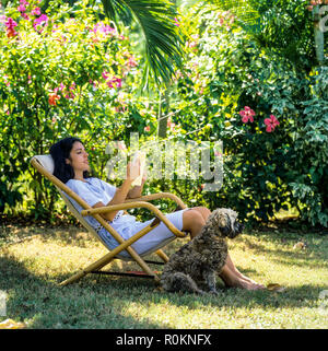 Young woman sitting in deck chair and reading a book, dog, tropical garden, Guadeloupe, French West Indies,