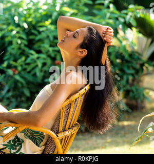 Young woman brushing her hair, tropical garden, Guadeloupe, French West Indies, - Stock Photo