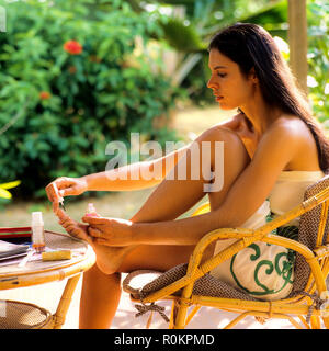 Young woman applying nail varnish on her toenails, tropical garden, Guadeloupe, French West Indies, - Stock Photo
