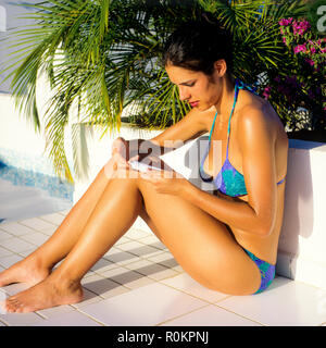 Young woman with blue bikini applying sun cream, poolside, Guadeloupe, French West Indies, - Stock Photo