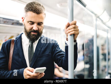 Hipster businessman with smartphone inside the subway in the city, travelling to work. - Stock Photo