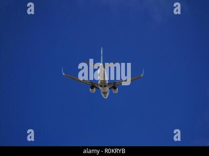 Plane flying with clearly sky in Alicante - Stock Photo