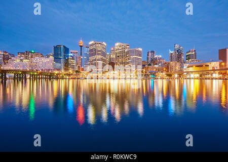 Skyline with skyscrapers in Darling Harbour at dusk, Sydney, New South Wales, Australia - Stock Photo