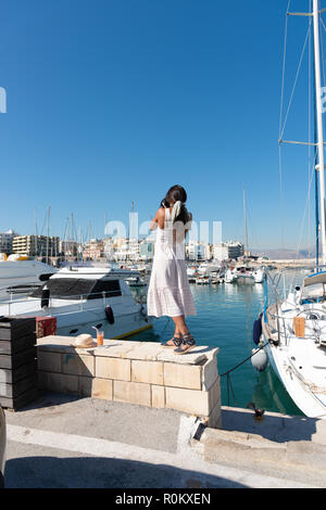 Traveling tourist woman on vacation in Heraklion Crete walking at the port. Lovely elegant girl in beige dress visiting the famous Mediterranean Venet - Stock Photo
