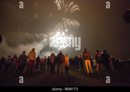 People looking at fireworks while gathering to celebrate the Bonfire and fireworkdisplay in Roundhay Park, Leeds. - Stock Photo