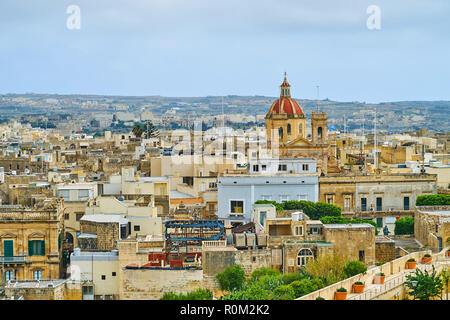 The red dome of St George parish church rising above the roofs of Victoria, Gozo Island, Malta. - Stock Photo