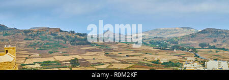 Panorama of Gozo farmlands on the foggy weather, the rocks and the famous Tas-Salvatur (Tal-Merzuq) Hill can be seen on the background, Malta. - Stock Photo