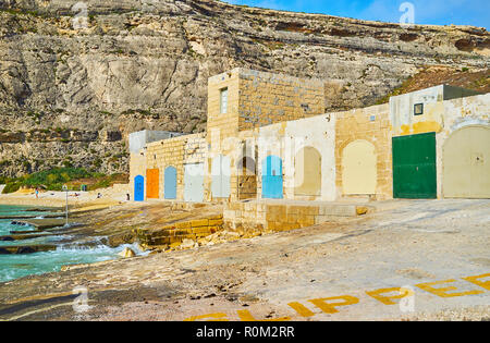 The stone boat houses with colorful doors located on shore of Dwejra Inland Sea - the famous tourist site on Gozo Island, Malta. - Stock Photo