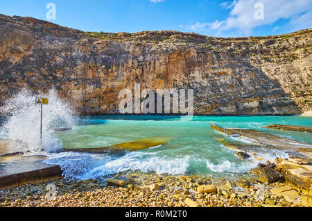 The foamy waves splash against the beach of Dwejra Inland sea, the massive rock with Blue Hole grotto is seen on the background, San Lawrenz village,  - Stock Photo