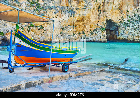 The colored wooden Maltese luzzu boat on shore of Dwejra Inland sea with a view on Blue Hole grotto on the background, San Lawrenz, Gozo, Malta. - Stock Photo