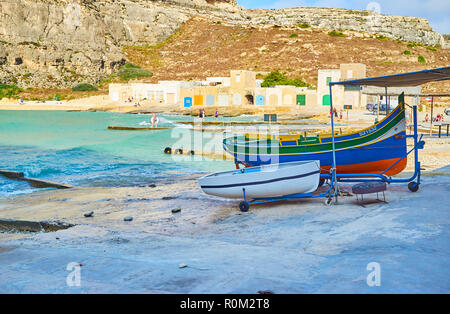 SAN LAWRENZ, MALTA - JUNE 15, 2018: The picturesque small San Lawrenz fishing village with old boat houses and traditional luzzu boats along the shore - Stock Photo