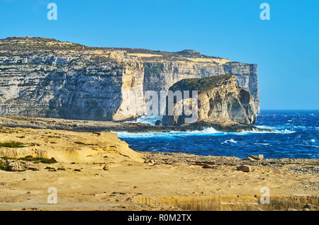 The tall cliffs and beautiful Fungus Rock (General's Rock) on the coast of Dwejra Bay, famous for Azure Window site and Dwejra Inland Sea, San Lawrenz - Stock Photo