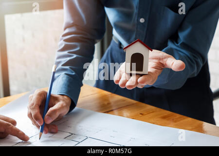 Architect or engineer using pen working on blueprint, architectural concept - Stock Photo