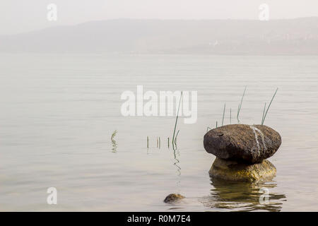 3 May 2018 Rocks piled together in flat calm shallows of the Sea Of Galilee Israel Israel on a hot hazy afternoon - Stock Photo