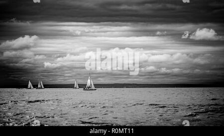 Boat sailing in the upcomming storm. Sailboat in bad weather sail at opened sea. Sailing yacht under heavy cloud sky. - Stock Photo