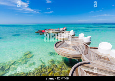 Chill zone, over water wooden pier, jetty in Maldives. Loungers and over water hammock, amazing blue sea in luxury tropical resort. Beach vacation - Stock Photo