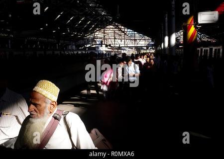 Through the roof of Chhatrapati Shivaji Maharaj Terminus, the busiest rail station, Mumbai, India, a beam of light illuminates disembarking commuters - Stock Photo