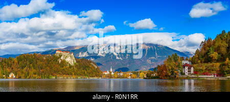Lake Bled in Slovenia panoramic view with castle, town and autumn trees in Julian Alps mountains - Stock Photo