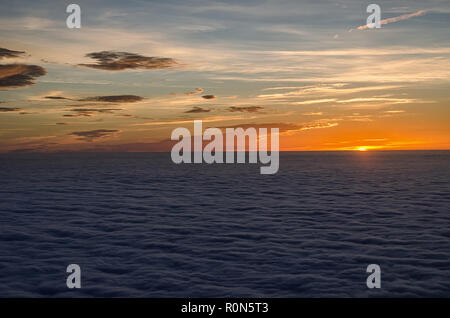 sun setting in the sea of clouds with beautiful and colorful sky above - Stock Photo