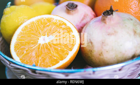 Pomegranates, oranges and lemons in a wicked basket on a wooden table of a rustic kitchen. Autumn background with blank copy space for editor's text. - Stock Photo