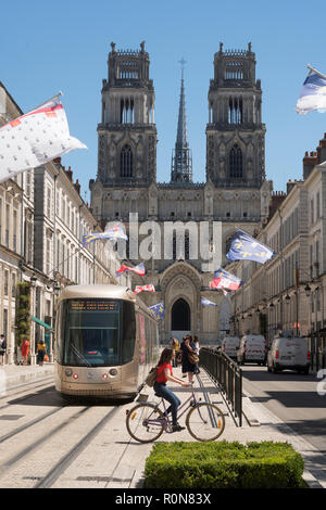 Female cyclist crossing Rue Jeanne d'Arc in front of a tram, Orléans, Centre-Val de Loire, France, Europe - Stock Photo