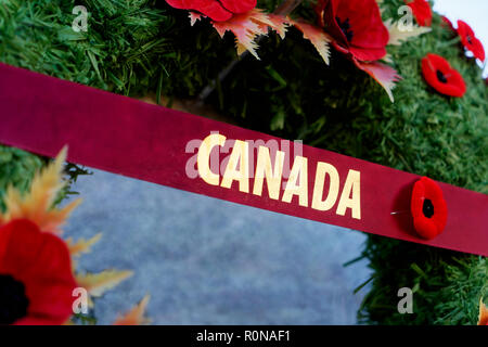 Remembrance Day wreath covered in poppies hanging on a Canadian war memorial. - Stock Photo