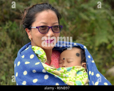 Young Northeast Indian Apatani tribal woman from Ziro holds in her arms a sleeping baby with two black dots of kohl against evil eyes (nazar utarna). - Stock Photo