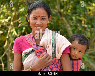 Young Northeast Indian Mishing tribal woman from Majuli Island carries her curious baby boy in a baby sling on her back. - Stock Photo