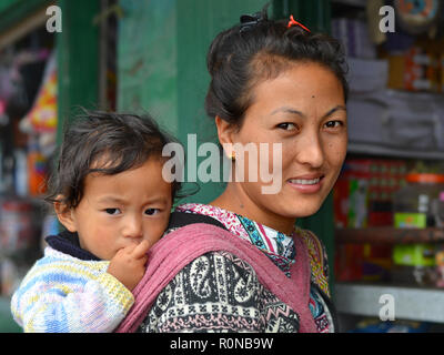 Young Northeast Indian Monpa hill-tribe woman carries her toddler boy in a traditional baby sling on her back. - Stock Photo