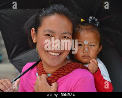 Young Indian Monpa hill-tribe woman carries her toddler girl in a traditional baby sling on her back. - Stock Photo