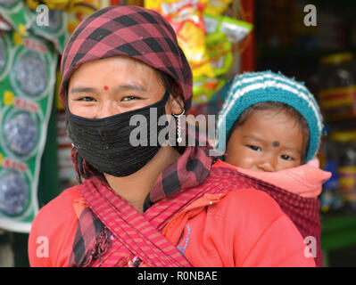 Young Northeast Indian minority woman with a black protective face mask carries her child in a baby sling on her back. - Stock Photo