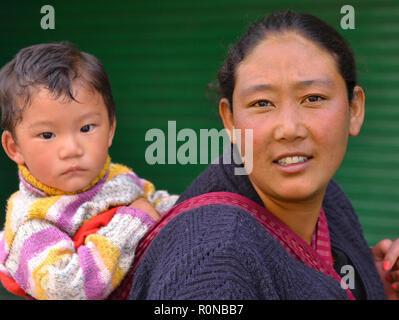 Young Indian Monpa hill-tribe woman carries her toddler boy in a traditional baby sling on her back. - Stock Photo