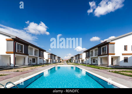 Communal swimming pool for residents of a newly built apartments site - Stock Photo