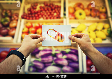Hands holding a paper sheet with vitamins supplement capsule over market shelves background with fresh fruits and vegetables. Nutrition pill as as nat - Stock Photo