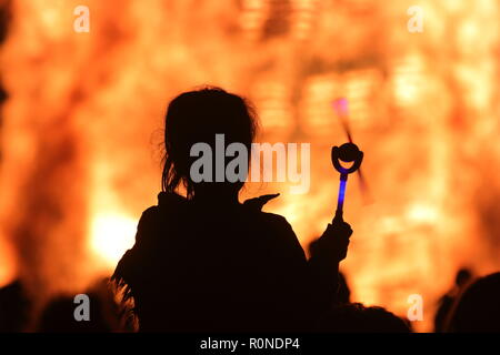 People silhouetted against a bonfire at Springhead Park, Rothwell , Leeds, West Yorkshire - Stock Photo