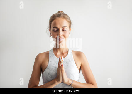 Young attractive Yoga teacher female greeting at the begining of practicing yoga - Stock Photo