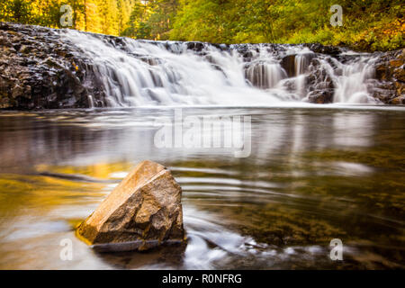 A small cascade along the Eagle Creek Trail in Oregon, USA, with focus on the rock in the foreground - Stock Photo