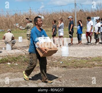 Residents carry Meals Ready to Eat to their vehicles at an emergency distribution point run by FEMA in the aftermath of Typhoon Yutu November 3, 2018 in Saipan, Commonwealth of the Northern Mariana Islands. The islands were devastated by Typhoon Yutu, the strongest typhoon to impact the Mariana Islands on record. - Stock Photo