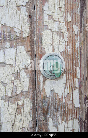 Corroded old lock and key in a wooden door with flaking paint - Stock Photo
