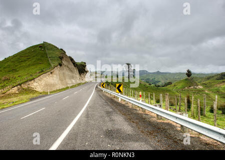 An asphalt road running through green countryside on an overcast day - Stock Photo