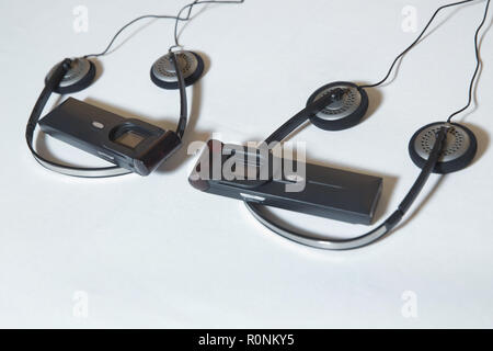 A set of headphones for simultaneous translation during negotiations in foreign languages . wireless multy language headphones set on the chairs in conference room - Stock Photo