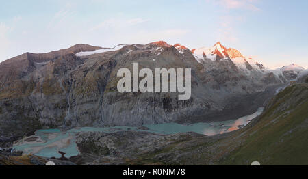 panoramic view of Austria's highest mountain Grossglockner  with declining Pasterze glacier, leaving behind a glacier lake - Stock Photo