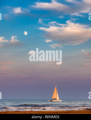 A sailboat on the sea with the nearly full moon in the sky above which is blue, pink and purple from the sun setting - Stock Photo