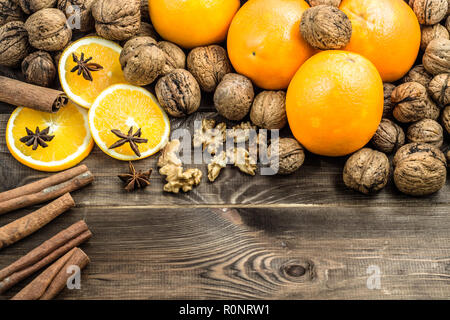 Traditional christmas spices and fruit on rustic wooden background with cinnamon, star anise, oranges and nuts, overhead - Stock Photo
