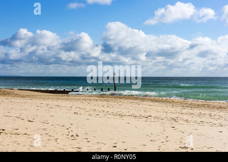 View of Bournemouth beach in autumn with waves breaking over a groyne & fluffy cumulus clouds on a sunny day, Dorset, UK - Stock Photo