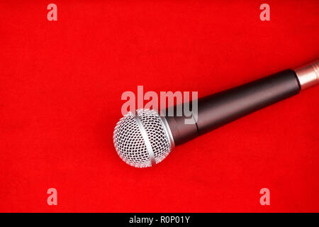 dynamic microphone on red floor for music background - Stock Photo