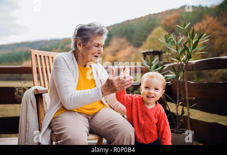 Elderly woman with a toddler great-grandchild on a terrace in autumn, giving high five. - Stock Photo